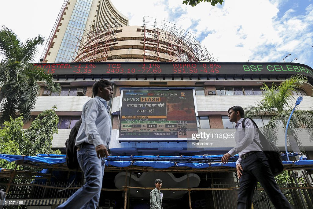 Pedestrians walk past an electronic ticker board displaying stock figures for Tata Steel Ltd., from left, Tata Consultancy Services Ltd. (TCS), and Wipro Ltd. at the Bombay Stock Exchange (BSE), center, in Mumbai, India, on Monday, June 27, 2016. Most Indian stocks advanced, led by companies tied to the economy, as some investors judged Friday's Brexit-induced selloff is overdone. TCS and Infosys Ltd., India's top software exporters that earn about a quarter of their revenue from Europe, were the biggest losers on the benchmark S&P BSE Sensex. Photographer: Dhiraj Singh/Bloomberg via Getty Images