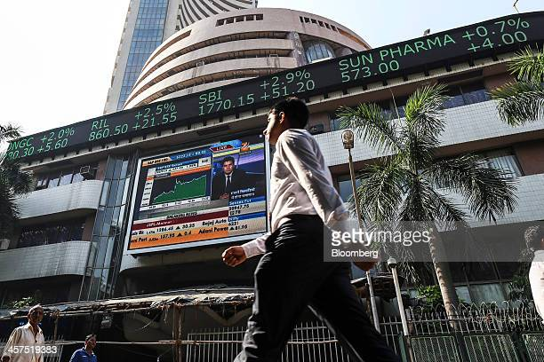 Pedestrians walk past an electronic ticker board that indicates stock figures for Oil Natural Gas Corp from left Reliance Industries Ltd State Bank...