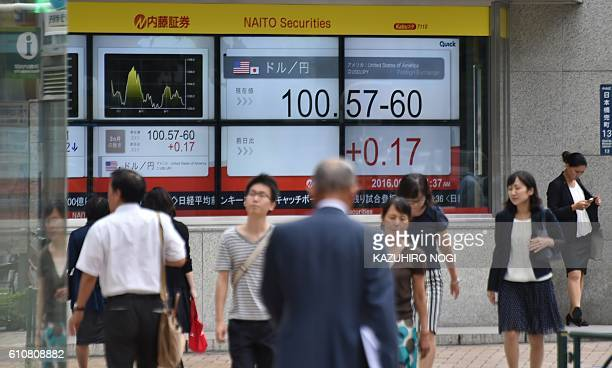 Pedestrians walk past an electronics quotation board displaying the current exchange rate of the Japanese yen against the US dollar in Tokyo on...