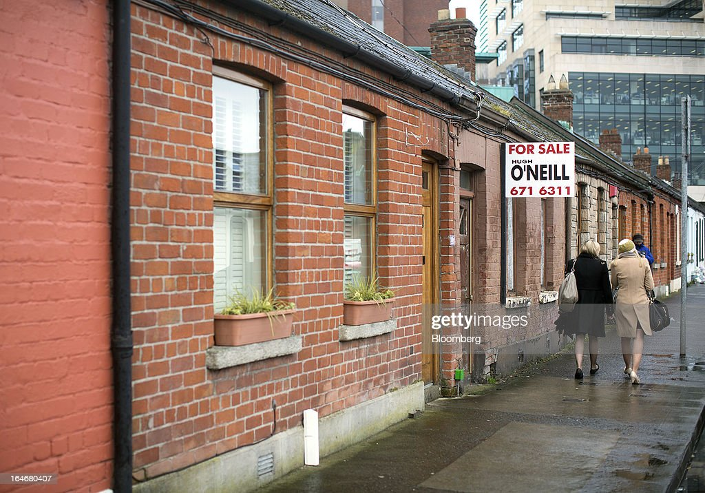 Pedestrians walk past an estate agent's board advertising a property 'For Sale' on a row of terraced houses in Dublin, Ireland, on Friday, March 15, 2013. Ireland's renewed competiveness makes it a beacon for the U.S. companies such as EBay, Google Inc. and Facebook Inc., which have expanded their operations in the country over the past two years. Photographer: Simon Dawson/Bloomberg via Getty Images