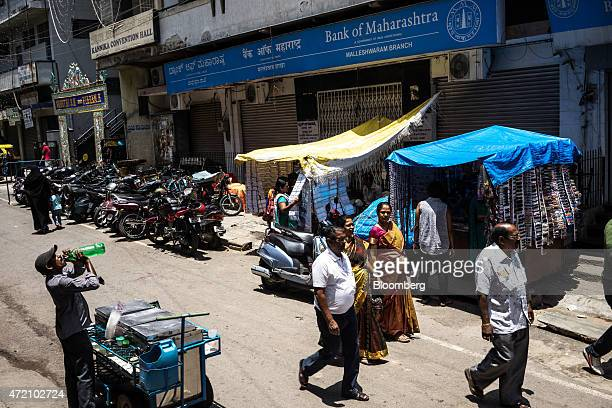 Pedestrians walk past an ice ream vendor drinking water and a Bank of Maharashtra Ltd branch in the Malleswaram district of Bangalore India on Sunday...