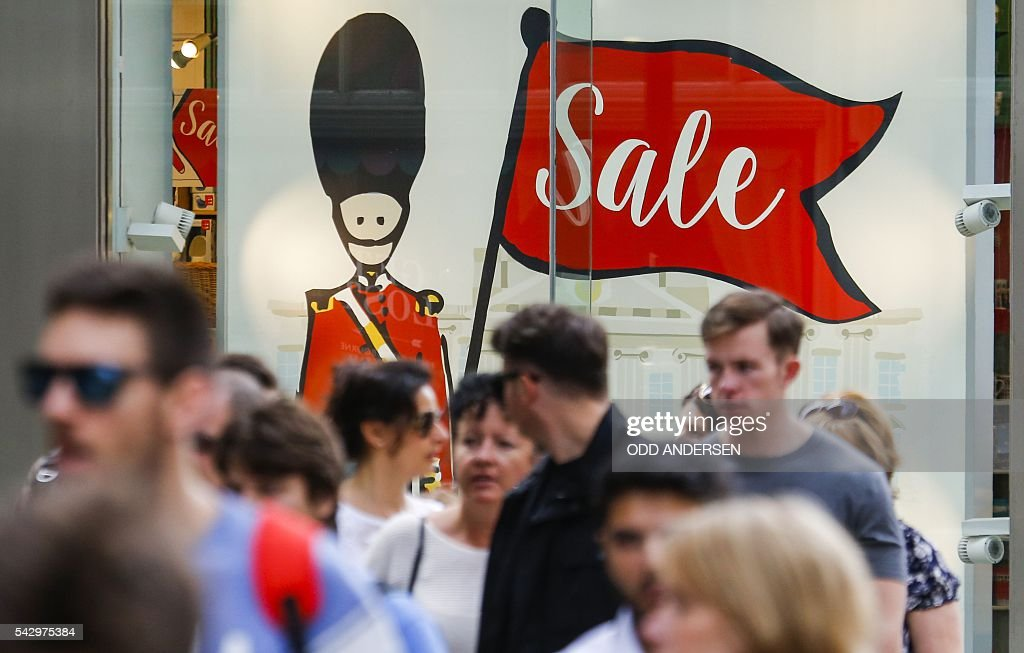 Pedestrians walk past an illustration of a British Queen's Guard soldier in the window of a store in central London on June 25, 2016, after the announcement that the UK had voted on June 23 to leave the European Union in a national referendum. The result of Britain's June 23 referendum vote to leave the European Union (EU) has pitted parents against children, cities against rural areas, north against south and university graduates against those with fewer qualifications. London, Scotland and Northern Ireland voted to remain in the EU but Wales and large swathes of England, particularly former industrial hubs in the north with many disaffected workers, backed a Brexit. / AFP / Odd ANDERSEN