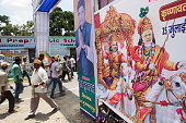 Pedestrians walk past an illustration of Indian Prime Minister Narendra Modi right as Lord Krishna sitting on a horse in Muzaffarpur Bihar India on...
