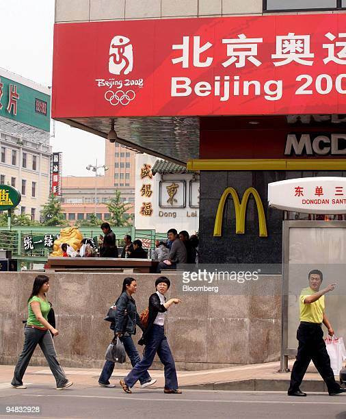 Pedestrians walk past an McDonald's Corp restaurant an Olympic sponsor in Beijing China on Monday May 19 2008 Twelve main sponsors paid an average...