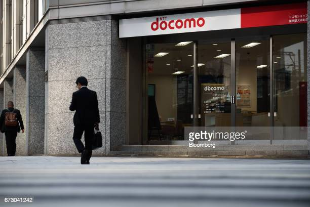 Pedestrians walk past an NTT Docomo Inc store in Tokyo Japan on Monday April 24 2017 NTT Docomo one of the world's largest wireless network operators...