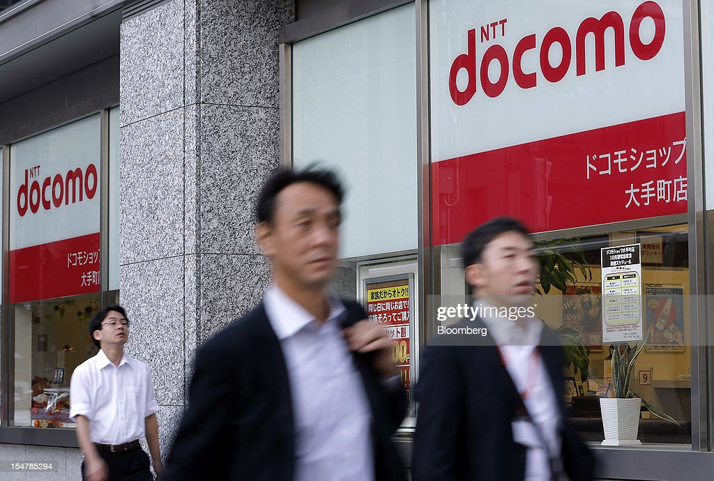 Pedestrians walk past an NTT DoCoMo Inc. store in Tokyo, Japan, on Friday, Oct. 26, 2012. NTT DoCoMo, Japan's largest mobile-phone company, cut its annual profit forecast 9 percent after competitors lured customers with Apple Inc.'s iPhone 5. Photographer: Kiyoshi Ota/Bloomberg via Getty Images
