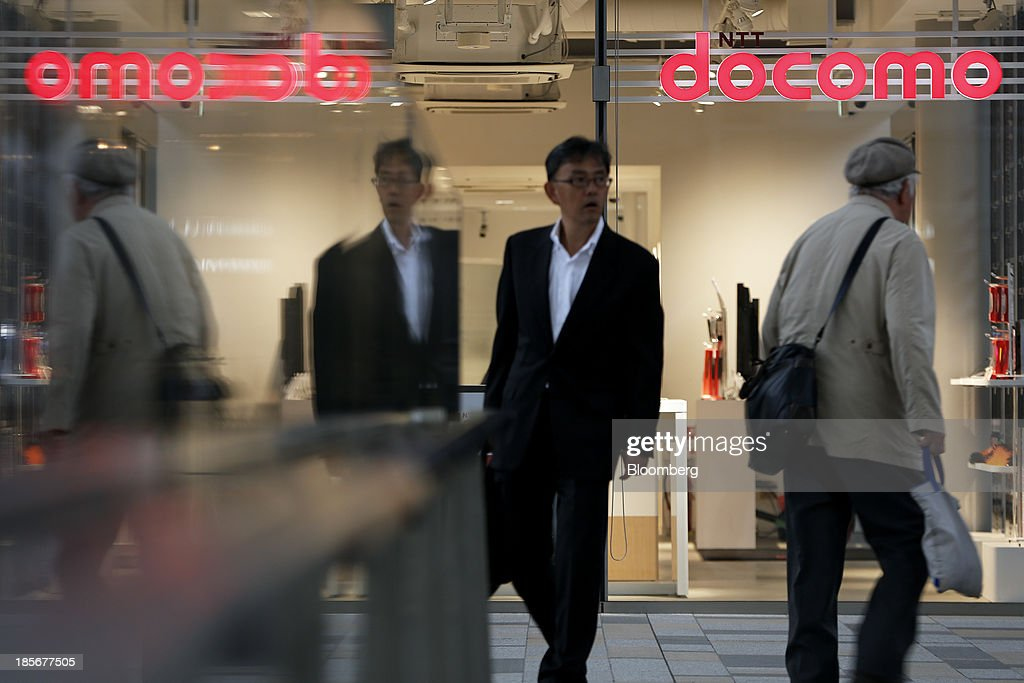 Pedestrians walk past an NTT Docomo Inc. store in Tokyo, Japan, on Wednesday, Oct. 23, 2013. DoCoMo, Japan's largest mobile phone carrier, is scheduled to release earnings results on Oct. 25. Photographer: Kiyoshi Ota/Bloomberg via Getty Images