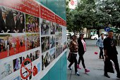 Pedestrians walk past antiterror propaganda posters pasted along the streets of Urumqi farwest China's Xinjiang region on September 16 2014 Ilham...