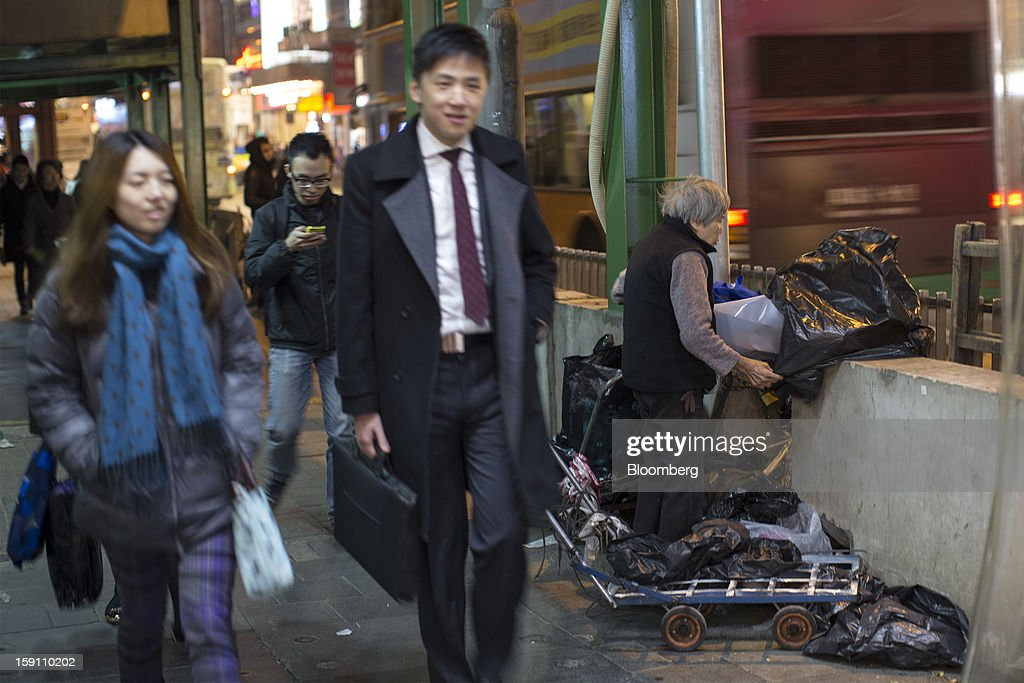 Pedestrians walk past as an elderly woman collects waste for recycling in Hong Kong, China, on Friday, Jan. 4, 2013. Chief Executive Leung Chun-ying, who has been buffeted by student protests and low popularity since taking office on July 1, has pledged to tackle Asia's biggest wealth gap as the division between poor and rich widened to its worst level since at least 1971. Photographer: Jerome Favre/Bloomberg via Getty Images