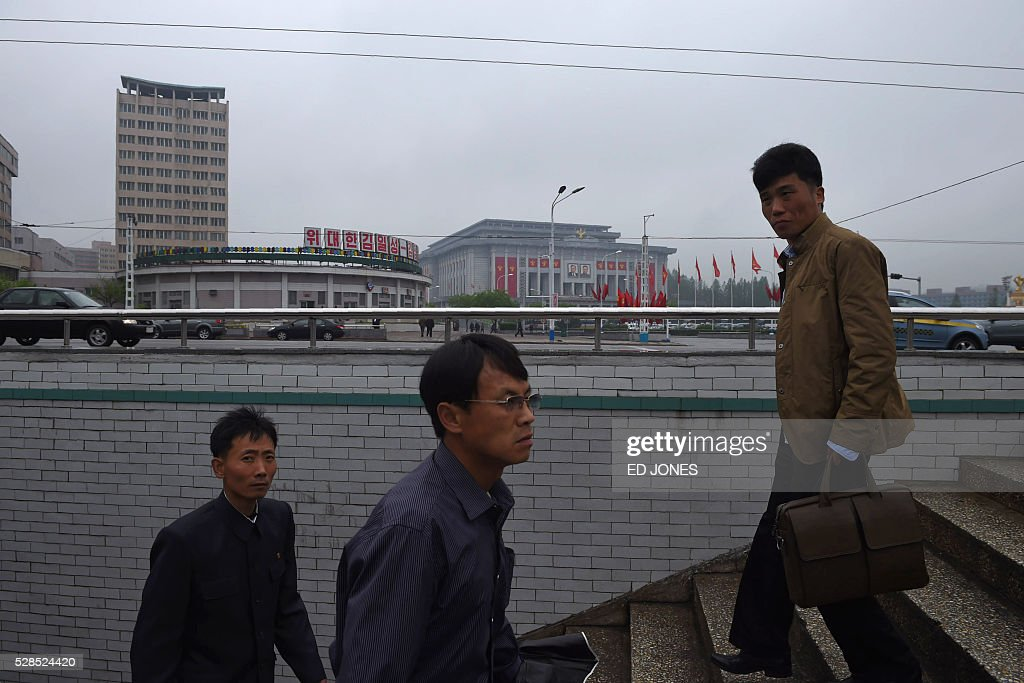 Pedestrians walk past as The April 25 Palace, venue of the Workers' Party Congress, is seen in the background at right ahead of the event in Pyongyang on May 6, 2016. North Korea will on May 6 launch its highest-level ruling party meeting in almost 40 years, with delegates set to heap praise on its nuclear arsenal as a 'precious sword' amid fears of a fresh atomic test. / AFP / Ed Jones