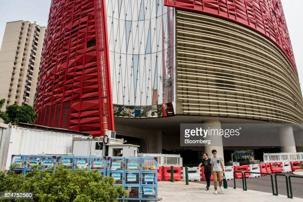 Pedestrians walk past barricades at the entrance to The 13 Hotel developed by 13 Holdings Ltd in the Coloane Village district of Macau China on...
