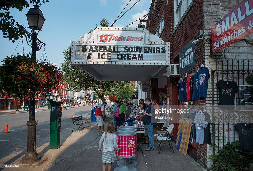 Pedestrians walk past baseball themed businesses on Main Street in Cooperstown New York US on Saturday July 26 2014 President Obama during a visit to...