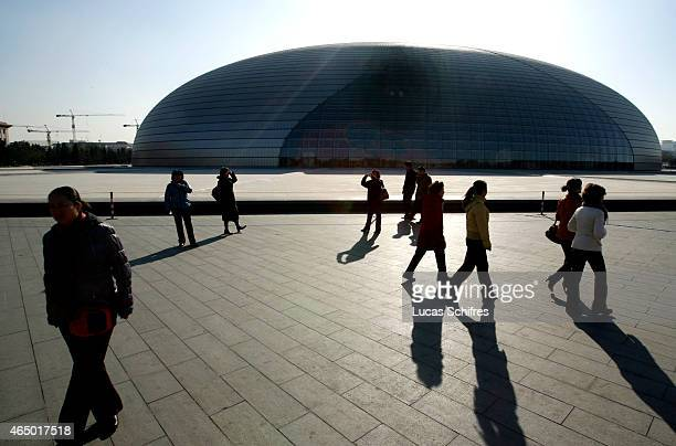 Pedestrians walk past Beijing National Grand Theatre on November 20 2008 in Beijing China The National Centre for the Performing Arts was designed by...