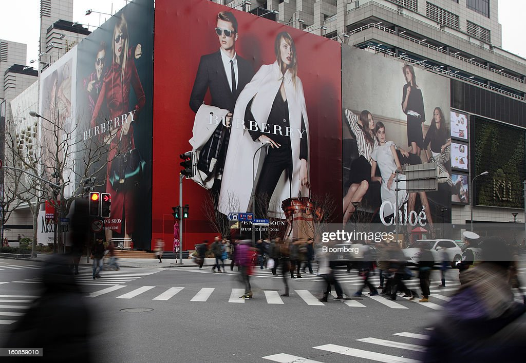 Pedestrians walk past billboards for Burberry Group Plc, left, and Cie. Financiere Richemont SA's Chloe brand outside a shopping mall under construction in Shanghai, China, on Wednesday, Feb. 6, 2013. China's economic growth accelerated for the first time in two years as government efforts to revive demand drove a rebound in industrial output, retail sales and the housing market. Photographer: Tomohiro Ohsumi/Bloomberg via Getty Images