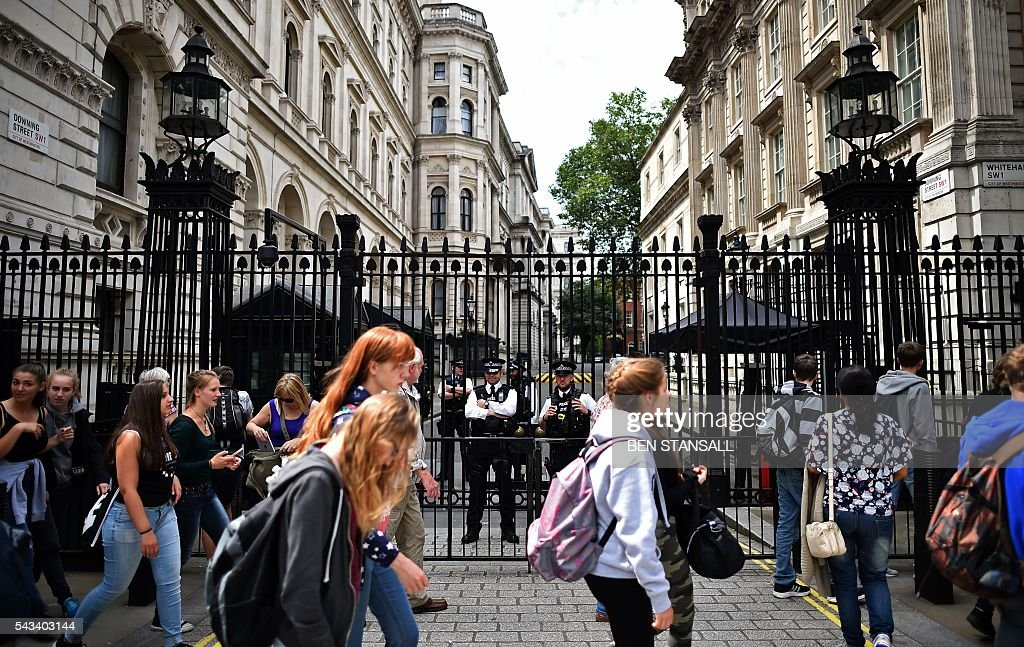 Pedestrians walk past British Police officers as they stand on duty on Whitehall, outside the entrance to Downing Street, the official residence of British Prime Minister David Cameron, in central London on June 28, 2016. EU leaders attempted to rescue the European project and Prime Minister David Cameron sought to calm fears over Britain's vote to leave the bloc as ratings agencies downgraded the country. Britain has been pitched into uncertainty by the June 23 referendum result, with Cameron announcing his resignation, the economy facing a string of shocks and Scotland making a fresh threat to break away. / AFP / BEN