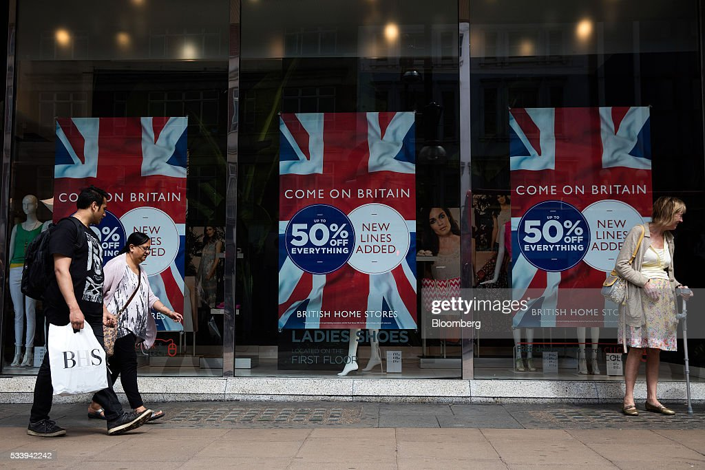 Pedestrians walk past British Union flag designs on advertisements for sales discounts in the windows of a BHS Ltd. retail store on Oxford Street in London, U.K., on Tuesday, May 24, 2016. U.K. retail sales began the second quarter with more momentum than economists forecast. Photographer: Simon Dawson/Bloomberg via Getty Images
