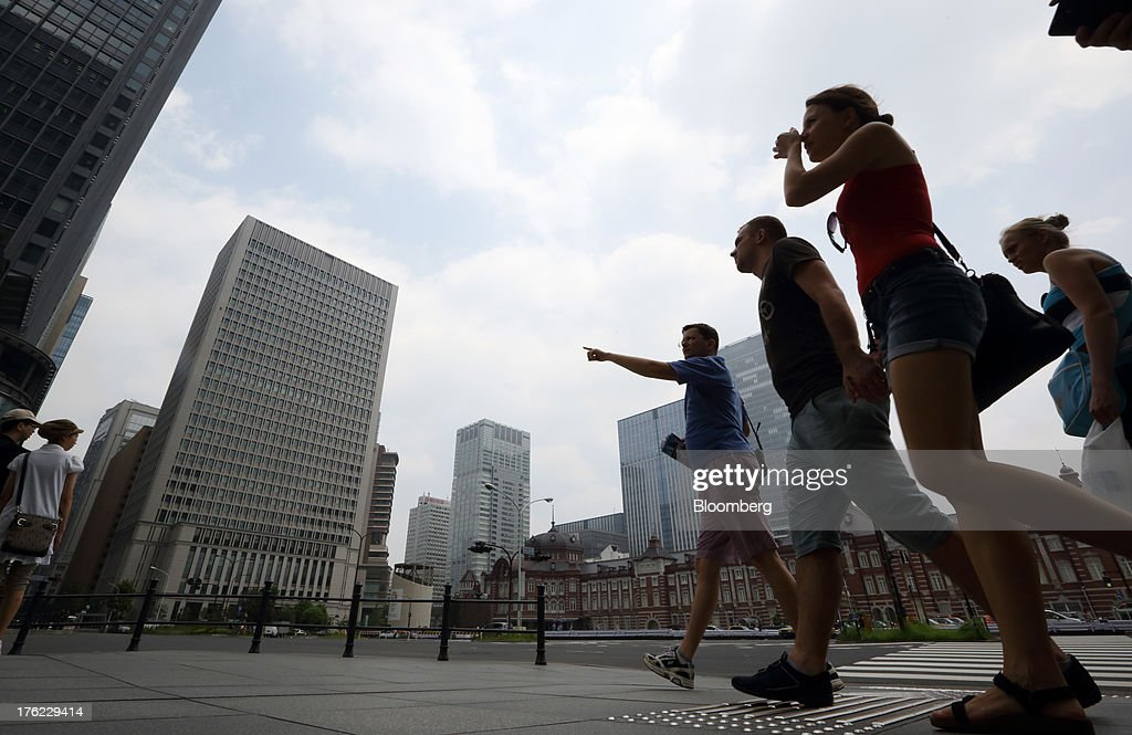 Pedestrians walk past buildings in the central business district of Tokyo, Japan, on Monday, Aug. 12, 2013. Japan's economy slowed more than forecast in the second quarter as businesses cut investment, undermining gains in consumer and government spending that helped reduce deflationary pressures. Photographer: Tomohiro Ohsumi/Bloomberg via Getty Images