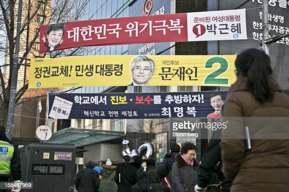 Pedestrians walk past campaign banners for South Korean presidential candidates Park Geun Hye from the ruling New Frontier Party top and Moon Jae In...