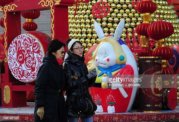 Pedestrians walk past Chinese Lunar New Year decorations featuring a statue on January 18 2011 of Lord Rabbit known as Tuer Ye a traditional icon of...