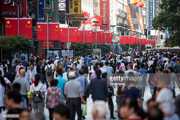 Pedestrians walk past Chinese national flags displayed along the Nanjing Road pedestrian street in Shanghai China on Friday Oct 2 2015 China's...