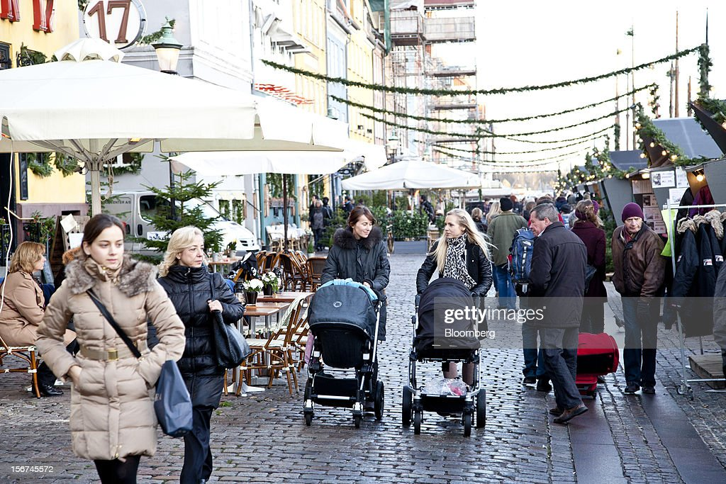 Pedestrians walk past Christmas market stalls on a cobbled street in the Nyhavn district of central Copenhagen, Denmark, on Monday, Nov. 19, 2012. Denmark's two-year yields sank to the lowest in almost three months in Copenhagen trading as Europe's debt crisis continues to drive investors north. Photographer: Linus Hook/Bloomberg via Getty Images