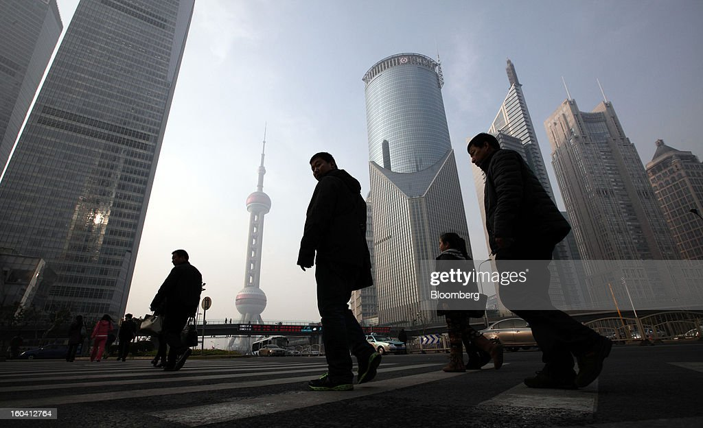 Pedestrians walk past commercial buildings in the Pudong area of Shanghai, China, on Wednesday, Jan. 30, 2013. China's economic growth accelerated for the first time in two years as government efforts to revive demand drove a rebound in industrial output, retail sales and the housing market. Photographer: Tomohiro Ohsumi/Bloomberg via Getty Images