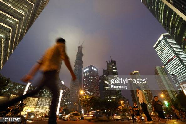 Pedestrians walk past commercial buildings including the Shanghai Tower center left as it stands under construction at night in the Lujiazui district...