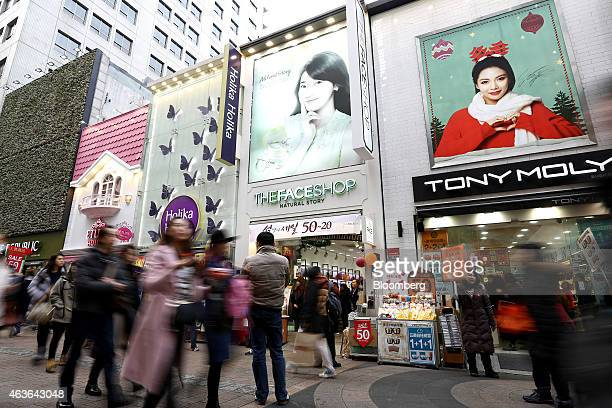 Pedestrians walk past cosmetic stores in the Myeongdong shopping district in Seoul South Korea on Sunday Feb 15 2015 South Korea kept its key...