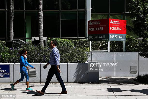 Pedestrians walk past Cushman Wakefield Inc signage in front of an office building for lease in the Brickell neighborhood of Miami Florida US on...