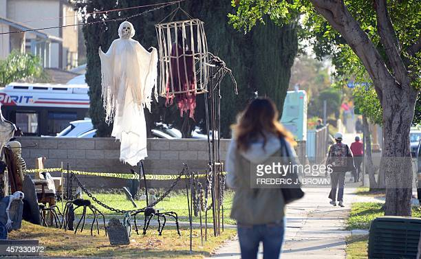 Pedestrians walk past decorations for Halloween in front of a home in Monterey Park California on October 16 2014 ahead of the annual end of the...