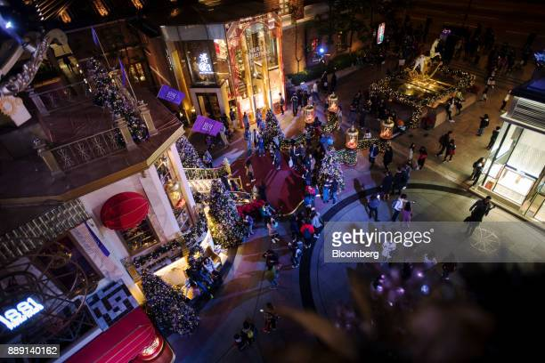 Pedestrians walk past festive Christmas decorations outside 1881 Heritage shopping mall operated by CK Asset Holdings Ltd in the Tsim Sha Tsui...