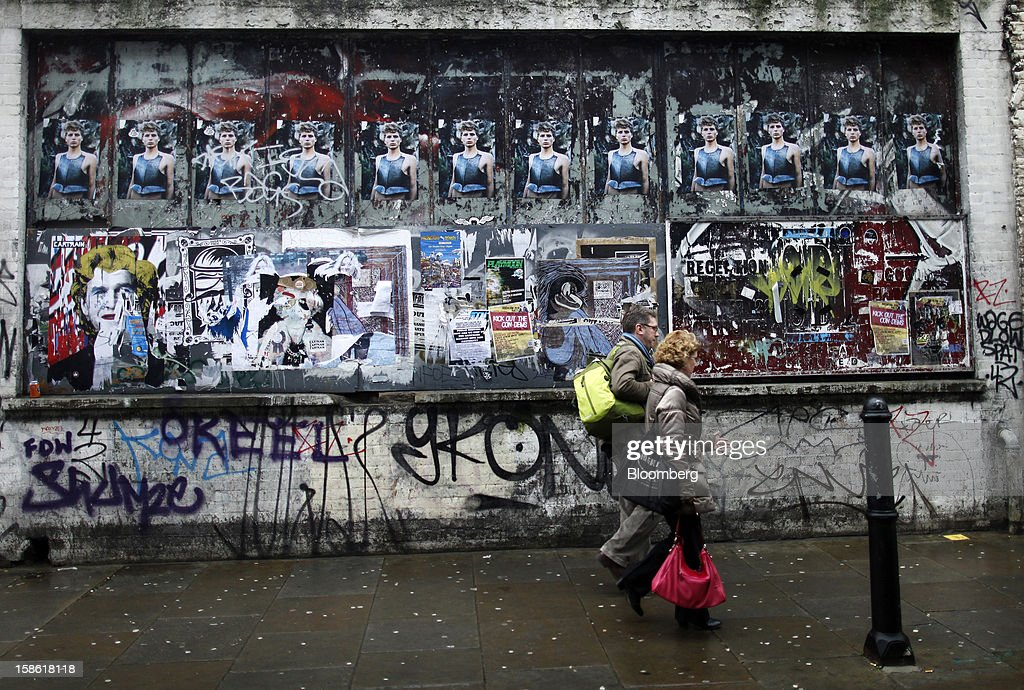 Pedestrians walk past fly posters and graffiti on a wall in London, U.K., on Thursday, Dec. 20, 2012. Britain's economy expanded less than previously estimated in the third quarter and the budget deficit unexpectedly widened in November, complicating Prime Minister David Cameron's attempts to bolster the recovery. Photographer: Simon Dawson/Bloomberg via Getty Images