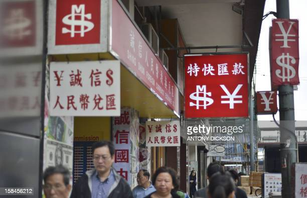 Pedestrians walk past foreign exchange signs in Hong Kong on December 17 2012 The yen plunged in Asian currency markets after Japan's conservative...