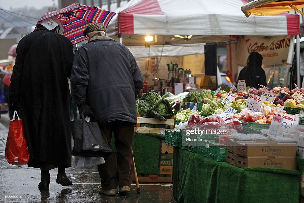 Pedestrians walk past fruit and vegetable goods displayed on a market stall in Guildford, U.K., on Friday, Dec. 14, 2012. Standard & Poor's lowered its outlook on Britain's top credit rating to negative, citing weak economic growth and a worsening debt profile. Photographer: Simon Dawson/Bloomberg via Getty Images