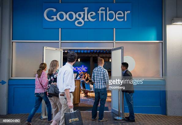 Pedestrians walk past Google Inc's Fiber Space in downtown Austin Texas US on Saturday April 4 2015 About 900000 people live in the city of Austin...