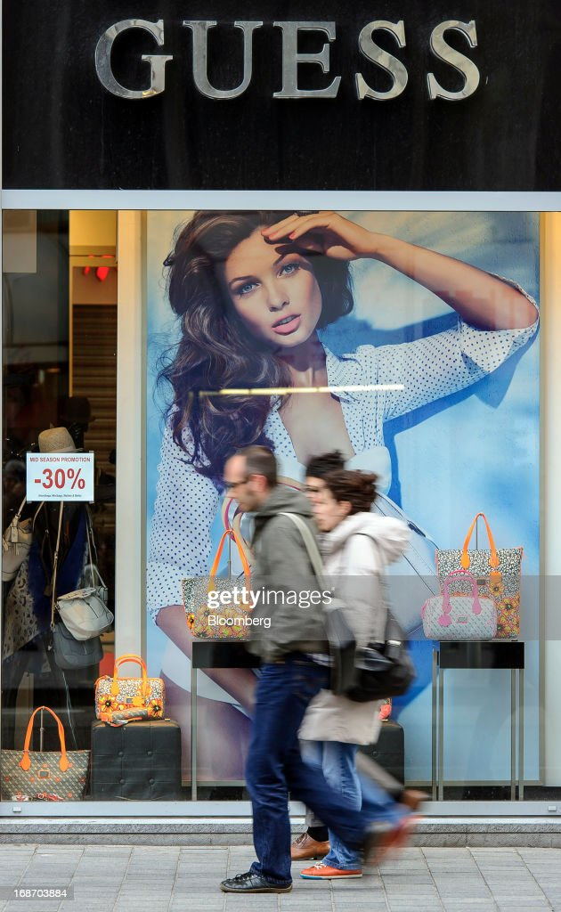 Pedestrians walk past handbags on display in the window of a Guess? Inc. store in Brussels, Belgium, on Monday, May 13, 2013. Euro-area data this week will probably reveal economic scars of the sovereign debt crisis confirming that the region is now suffering the longest recession since the single currency's creation. Photographer: Jock Fistick/Bloomberg via Getty Images