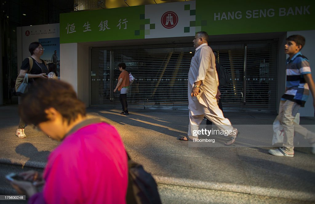 Pedestrians walk past Hang Seng Bank Ltd.'s headquarters in Hong Kong, China, on Monday, Aug. 5, 2013. Hang Seng Bank, the Hong Kong lender controlled by HSBC Holdings Plc, said first-half profit doubled to a record, beating the highest estimate in a survey on a one-time accounting gain and higher loan and fee income. Photographer: Lam Yik Fei/ Bloomberg