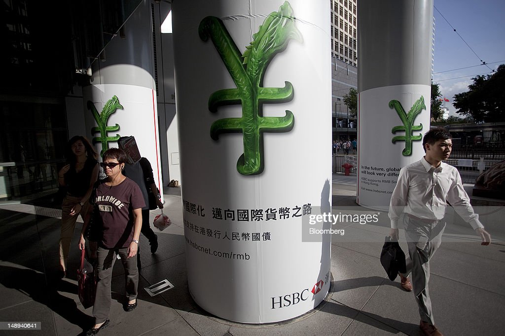 Pedestrians walk past HSBC advertisements showing a Renminbi currency symbol outside the HSBC Holdings Plc headquarters in Hong Kong, China, on Friday, July 20, 2012. Asian currencies had a second weekly advance on speculation the U.S. and China will adjust policies to revive the world's two biggest economies, boosting demand for riskier assets. Photographer: Jerome Favre/Bloomberg via Getty Images