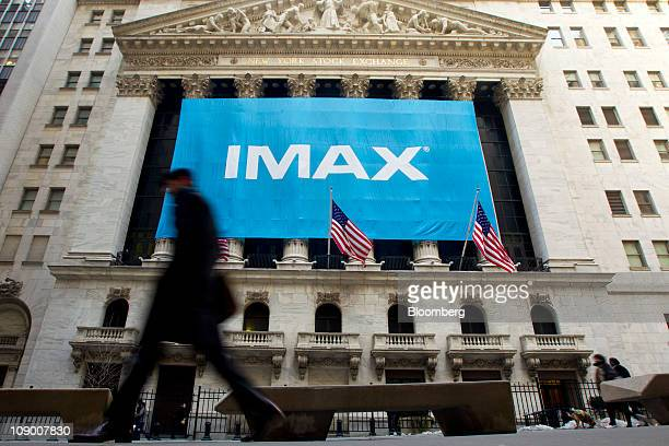 Pedestrians walk past Imax Corp signage displayed outside of the New York Stock Exchange in New York US on Friday Feb 11 2011 Imax plans to open more...