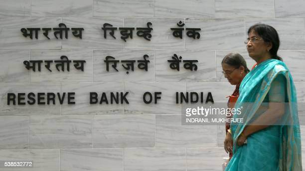 Pedestrians walk past India's central bank Reserve Bank of India logo in Mumbai on June 7 2016 The Reserve Bank of India has held its key interest...