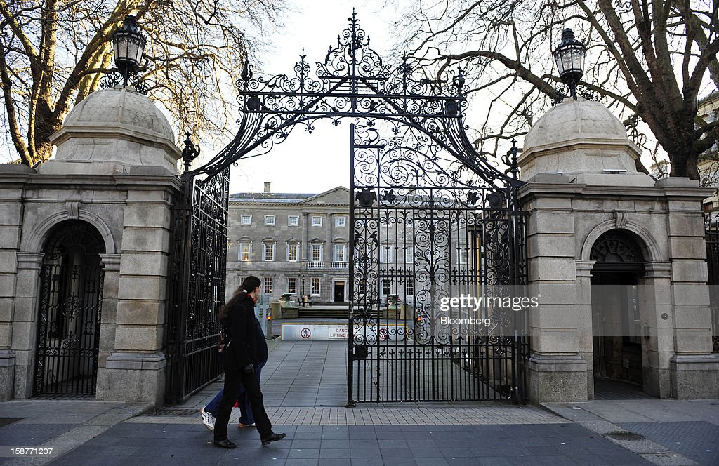 Pedestrians walk past iron gates at the entrance of the Irish parliament buildings in Dublin, Ireland, on Thursday, Dec. 27, 2012. Ireland will take over the EU presidency in January as the euro-area wrestles with putting the European Central Bank in charge of lenders within the currency union and other participating nations. Photographer: Aidan Crawley/Bloomberg via Getty Images