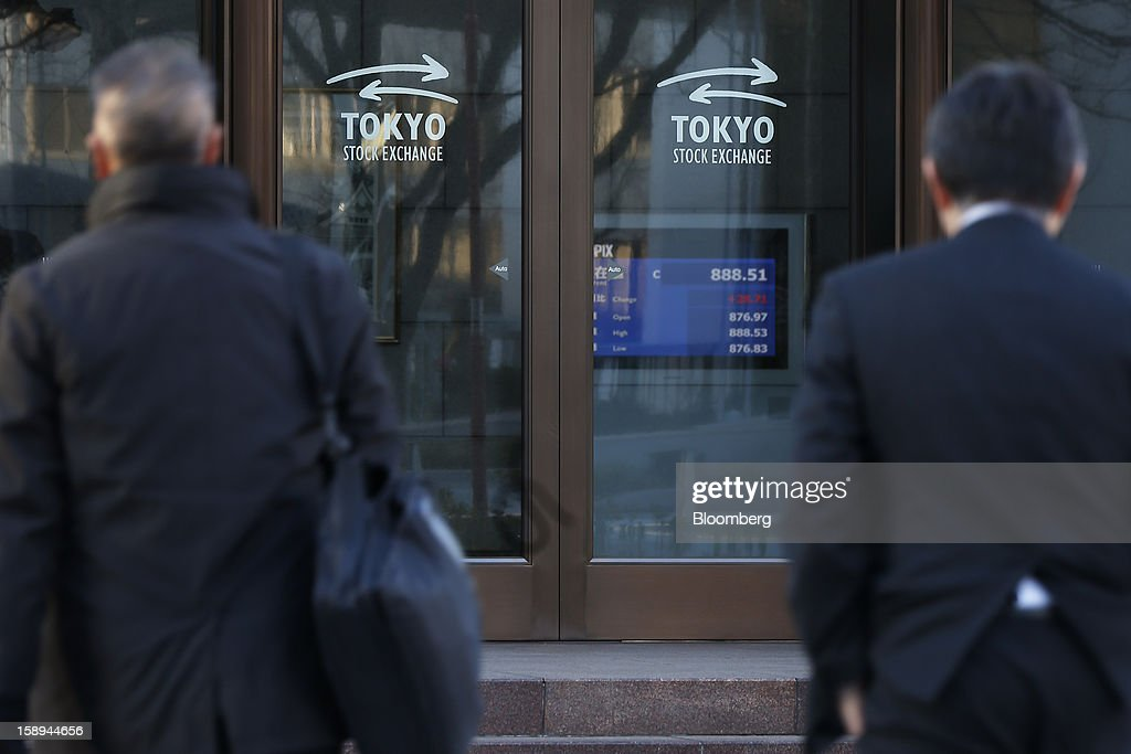 Pedestrians walk past Japan Exchange Group Inc.'s Tokyo Stock Exchange (TSE) on the first trading day of the year in Tokyo, Japan, on Friday, Jan. 4, 2013. Japan Exchange, created by the merger of Japan's two biggest bourses, fell in its trading debut on the Tokyo Stock Exchange. Photographer: Kiyoshi Ota/Bloomberg via Getty Images
