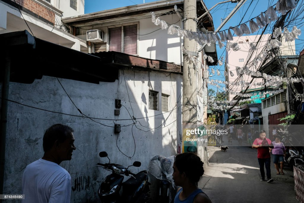Pedestrians walk past low-cost housing in Mandaluyong, Metro Manila, Philippines, on Tuesday, Nov. 14, 2017. Economists are forecasting the Philippines to be among the first to raise interest rates in the region and the International Monetary Fund saidlast week the central bank should be ready to tighten if there are signs of overheating. Photographer: Veejay Villafranca/Bloomberg via Getty Images