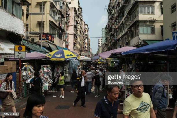 Pedestrians walk past market stalls on Apliu Street in the Sham Shui Po district of Hong Kong China on Saturday April 29 2017 Hong Kong a city of...
