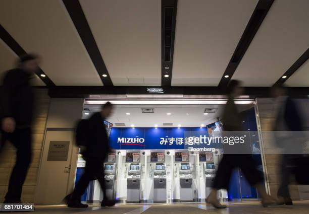 Pedestrians walk past Mizuho Bank Ltd automated teller machines outside the Mizuho Financial Group Inc headquarters building in Tokyo Japan on Friday...