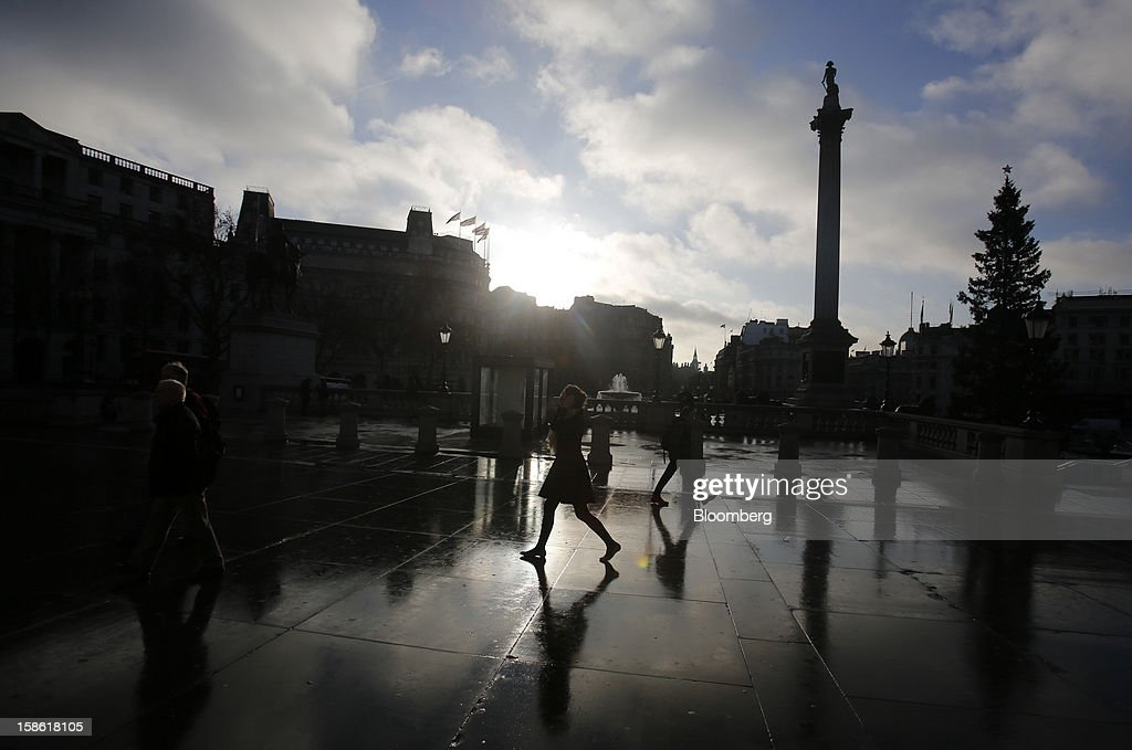 Pedestrians walk past Nelson's Column in Trafalgar Square in London, U.K., on Friday, Dec. 21, 2012. Britain's economy expanded less than previously estimated in the third quarter and the budget deficit unexpectedly widened in November, complicating Prime Minister David Cameron's attempts to bolster the recovery. Photographer: Simon Dawson/Bloomberg via Getty Images
