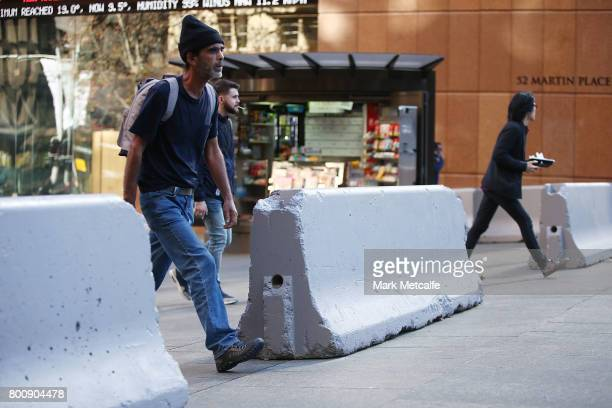 Pedestrians walk past newly installed anti terror bollards in Martin Place on June 26 2017 in Sydney Australia The large concrete blocks have been...