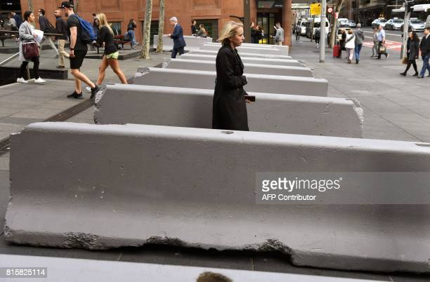Pedestrians walk past newlyinstalled concrete security bollards near the Lindt Cafe on July 17 scene of the 2014 Sydney cafe seige in which two...