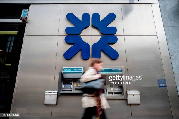 Pedestrians walk past offices of the Royal Bank of Scotland in central London on October 22 2017 / AFP PHOTO / Tolga Akmen