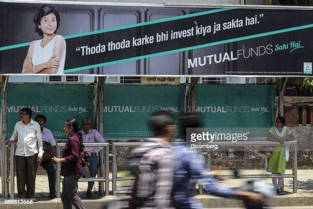 Pedestrians walk past passengers sitting next to an advertisement for the Mutual Funds Sahi Hai campaign by the Association of Mutual Funds in India...